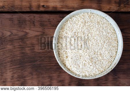Sesame Oilcake. Squeezed White Sesame In Clay Glazed Bowl On Wooden Background. Benne. Top View.
