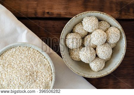 Sesame Seed Balls And Sesame Squeezed Seeds In Bowls On Linen And Wooden Background. Top View.