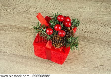A Red Square Gift, The Packaging On Which A Red Bow, Wooden Background