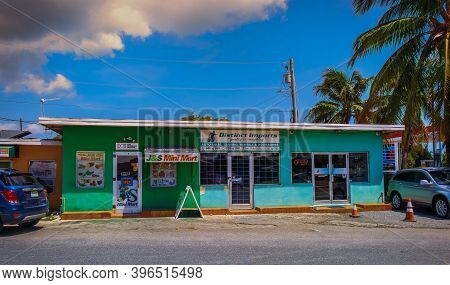 Grand Cayman, Cayman Islands, July 2020, View Of A Small Food Store And A Car Dealer Office In A Col