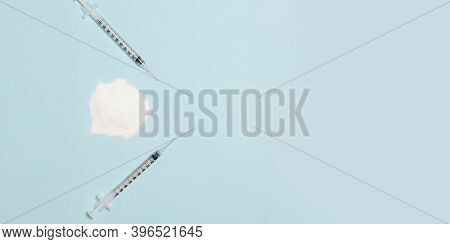Cocaine Or Heroin Narcotic Drug Powder And Two Syringes With A Needle On A Blue Background. Addictio