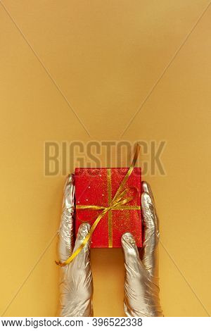 Hands In Golden Medical Gloves Holding Christmas Red Gift Box With Golden Bow On Gold Background. Ch