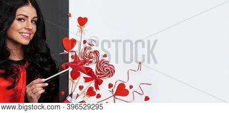 Woman with magic wand near Valentines day decoration and heart shaped lollipops isolated on white background