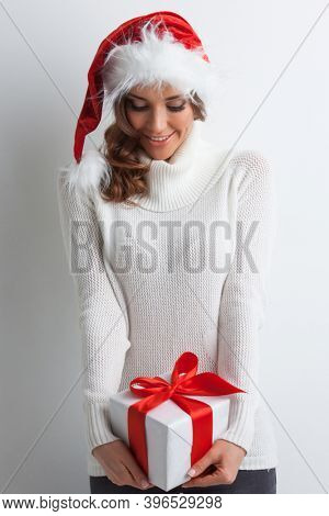 Smiling cute girl in Santa hat with red christmas gift box