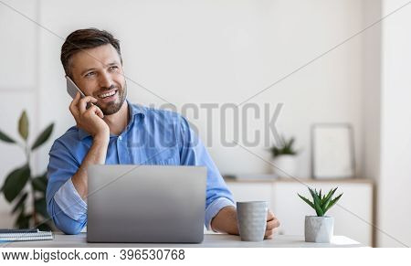 Handsome Male Entrepreneur Having Phone Conversation And Drinking Coffee At Workplace, Sitting At De
