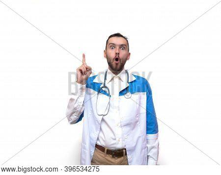 Portrait Of Doctor Man In Medical Coat Having Idea Moment Pointing Finger Up On White Studio Backgro