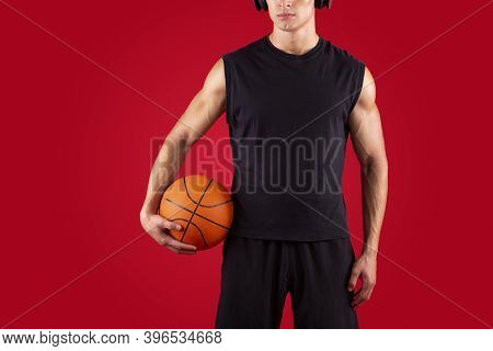 Cropped View Of Young Basketball Player Holding Ball, Listening To Music In Headphones Over Red Stud
