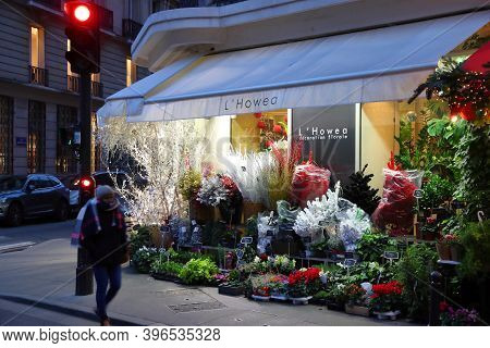 Paris, France - December 10, 2019: Person Walks By A Flower Shop In 7th Arrondissement Of Paris, Fra