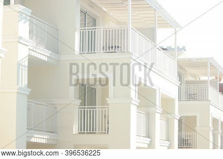 Modern Beautiful Hotel Resort Building With White Balconies. White Resort Hotel Facade With Terraces