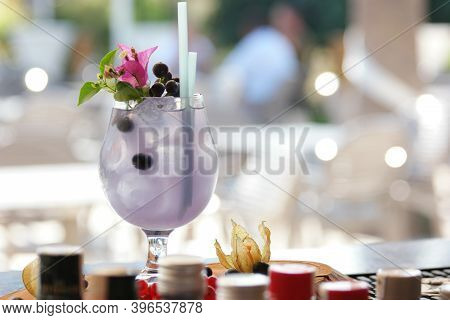 Summer Cold Drink With Blueberry, Ice And Pink Flower. Delicious Blueberry Cocktail At Restaurant. B