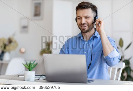 Hotline Operator. Handsome Young Man Customer Support Manager In Headset Working With Laptop Compute