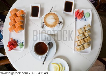 Japanese Sushi Rolls Served With Drinks On Cafe Table