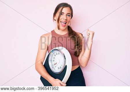 Beautiful young caucasian woman holding weight machine to balance weight loss screaming proud, celebrating victory and success very excited with raised arms