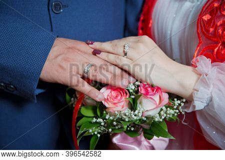 They Put Their Hands On The Red Rose . Bride And Groom With Engagement Gold Rings Put Their Hands .