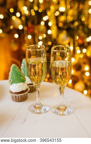 Champagne Glasses And The Lights On Christmas Tree On A Background