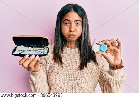 Young latin girl holding glasses and contact lenses puffing cheeks with funny face. mouth inflated with air, catching air.