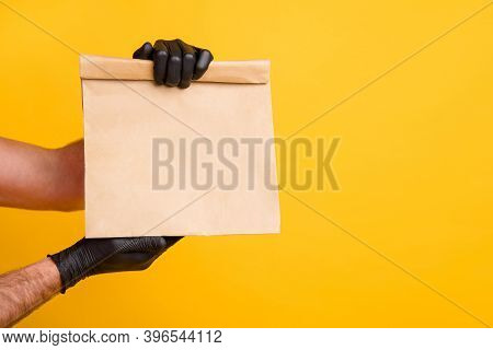 Cropped Photo Of Delivery Man Arms Hold Takeout Paper Package Wear Black Gloves Isolated Bright Yell