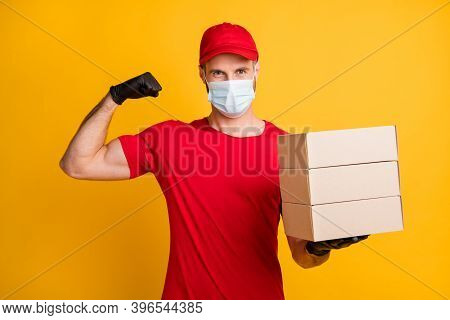 Photo Of Strong Postman Hold Pile Carton Boxes Raise Arm Show Biceps Wear Mask Red T-shirt Hat Isola