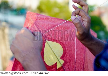 Man Threading A Paper And Wood Kite In Order To Fly It On The Indian Harvest Festival Of Makar Sankr