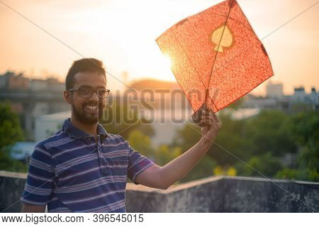 Young Man Holding Aloft Colorful Paper And Wood Kite Against A Blurred Background Setting Sun On The