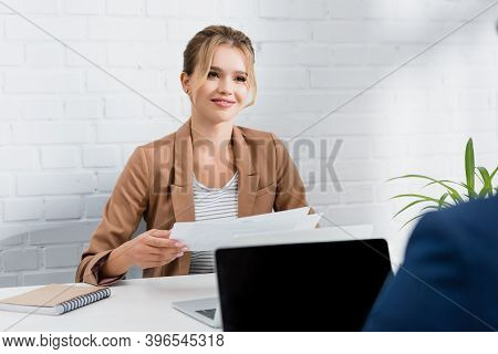 Businesswoman With Documents Looking At Co-worker, While Sitting At Table With Laptops On Blurred Fo