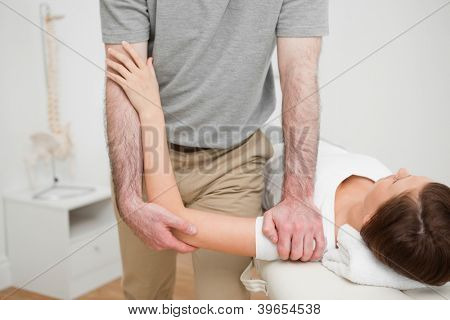 Physiotherapist pressing the shoulder of a woman in a medical room