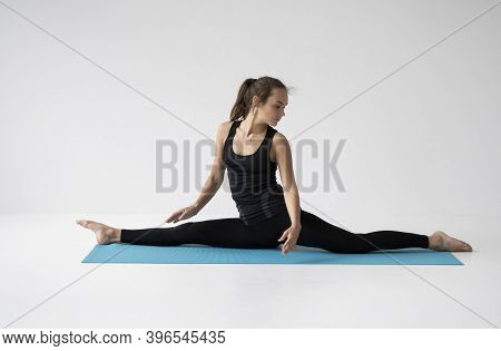 Young Woman Is Practicing Yoga In A Studio. Slim Young Girl In A Black Sport Wear Is Doing Yoga Prac