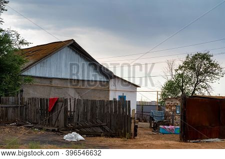 House In Countryside With A Tiled Roof And A Broken Wooden Fence