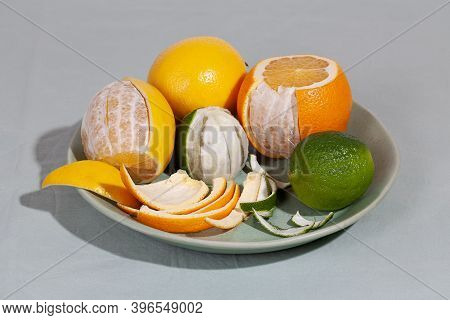 Fruit Citrus With Peels On Green Plate. Concept Reducing Food Waste