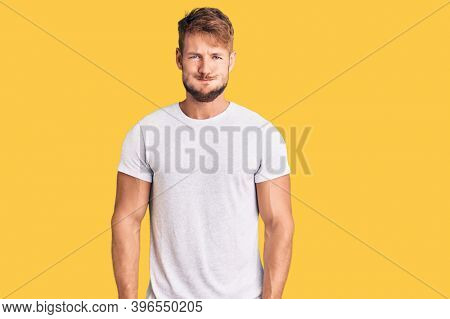 Young caucasian man wearing casual white tshirt puffing cheeks with funny face. mouth inflated with air, crazy expression.