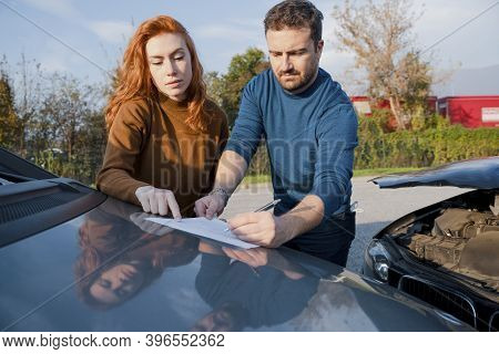 Man And Woman Reporting Damage After Car Accident