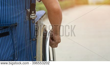 Rear View Of Disabled Man's Hand Manually Pushing Wheelchair On Pavement In Public Park, Close Up Wi