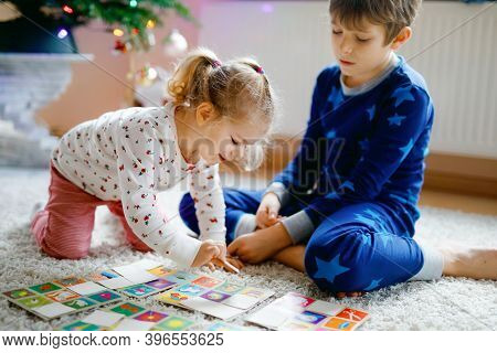 Two Little Chilren, Cute Toddler Girl And School Kid Boy Playing Together Card Game By Decorated Chr
