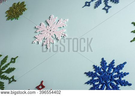Flatlay Multicolored Christmas Snowflakes On A Blue Background. View From Above