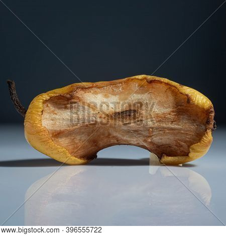 Stub Of Pear On A Gray Background, With Reflection. Minimalistic Concept