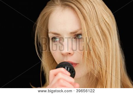 blond-haired woman singing against black background