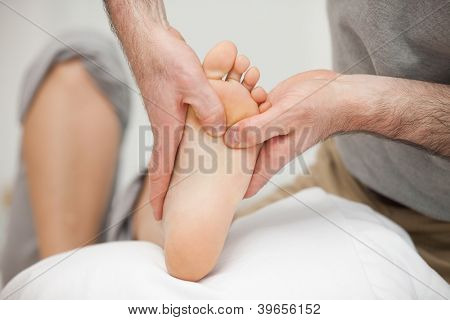 Chiropodist touching the foot of a woman in a medical room