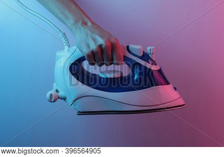 Hand Holds Iron For Ironing. Creative Pop Art Pink Blue Neon Color. Trendy Gradient Illumination. Ni