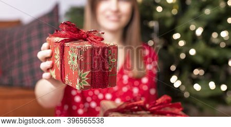 Cropped Caucasuian Woman Holding Or Showing Christams Gift Or Present Wrapped In Paper With Red Ribb