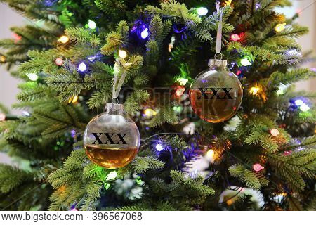 Whiskey Filled Christmas Ornaments. Clear Christmas Ornaments filled with Liquor hang from a light Christmas Tree. Christmas is the time for celebration and liquor.