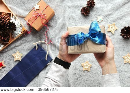Gift In Hand. Gift Wrapping Process. Blue Bow. Gifts In Craft Paper. Festive Atmosphere. New Year's