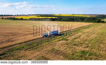 Tractor Pulling Trailer In Sunny Rural Field.