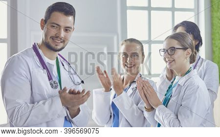 Happy Medical Team Comprising Male And Female Doctors Smiling Broadly And Giving A Thumbs Up Of Succ