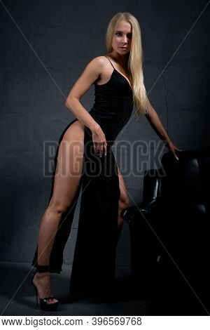 Attractive Blonde In An Elegant Evening Dress With A Large Slit On A Dark Background. Fashion Beauty