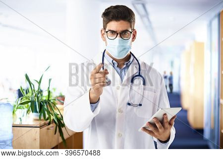 Shot Of A Male Doctor Wearing Face Mask And Pointing His Finger To You While Standing At Clinic Foye