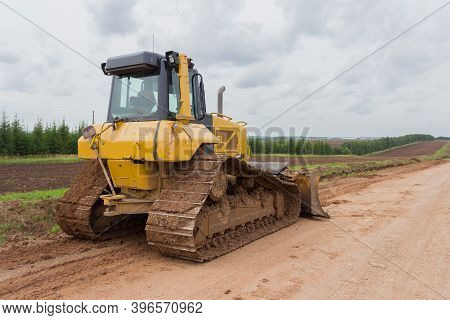 Bulldozer During Road Construction. Construction Machinery. Earth Moving By A Bulldozer In The Const