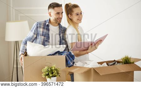 Portrait Of Happy Couple Looking At Laptop Computer Together Sitting In New House, Surrounded With B