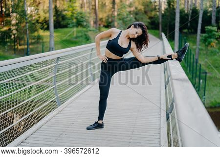 Determined Sportswoman Stretches Legs On Bridge, Wears Active Wear, Demonstrates Good Flexibility, P
