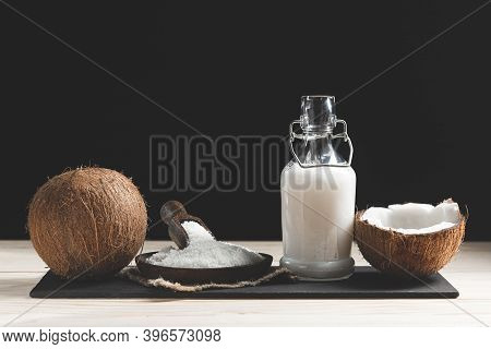 Coconuts, Coconut Milk And Grated Coconut On Dark Background.