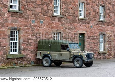 Fort George, Scotland - August 7, 2019: Land Rover Defender Army Vehicle In Front Of Red Brick Barra